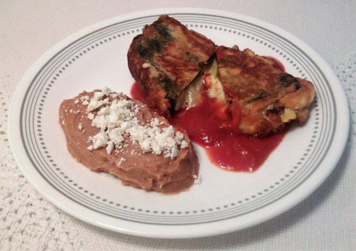 stuffed poblano with cheese served with refried beans and caldillo