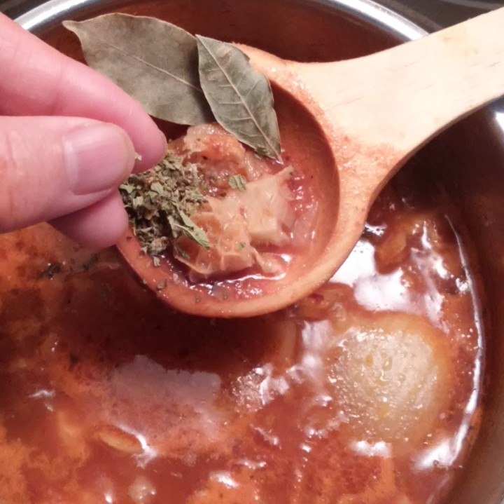 adding herbs to soup